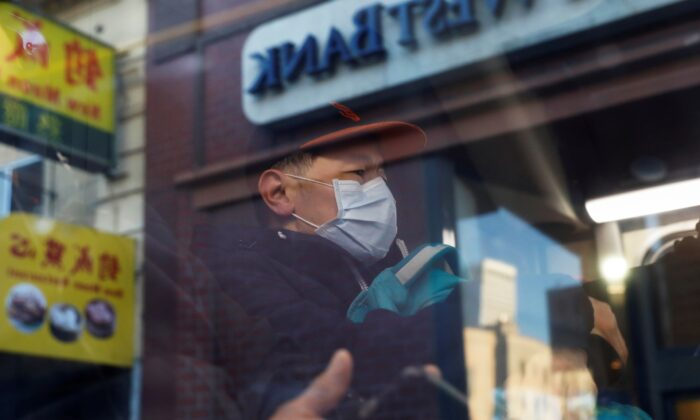 A man wears a face mask onboard a public bus in the Chinatown section of San Francisco, Calif., on Feb. 25, 2020. (Shannon Stapleton/Reuters)