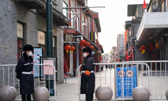 Chinese security guards wear protective masks as they stand on an empty commercial street on Feb. 25, 2020 in Beijing, China. (Lintao Zhang/Getty Images)
