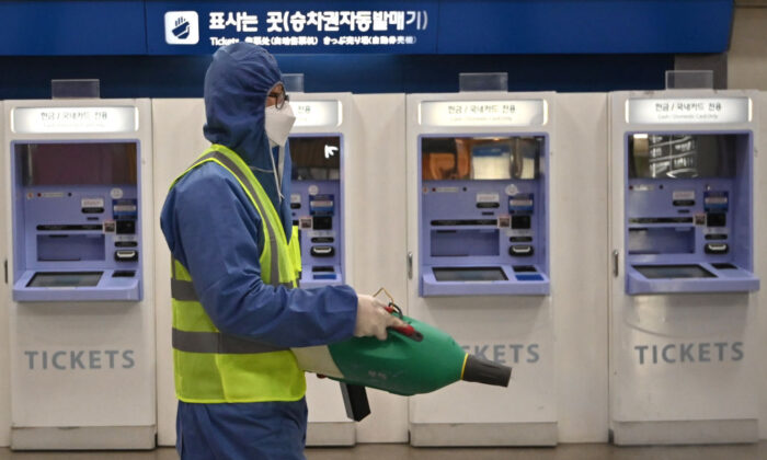 A worker wearing protective gear sprays disinfectant as part of preventive measures against the spread of the novel coronavirus at a railway station in Daegu, South Korea, on Feb. 26, 2020. (Jung Yeon-je/AFP via Getty Images)