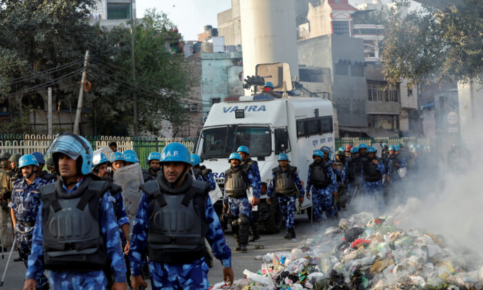 Members of Rapid Action Force move past smoldering debris after it was set on fire by demonstrators in New Delhi, India, on Feb. 25, 2020. (Danish Siddiqui/Reuters)