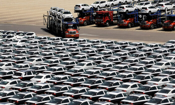 A carrier trailer transports newly manufactured cars at a port in Dalian, Liaoning Province, China on May 21, 2019. (Reuters)