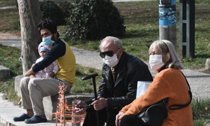 People with face masks sit outside of the hospital of Ahepa in Thessaloniki on Feb. 26, 2020, the same day the country reported its first case of the new coronavirus. (Sakis Mitrolidis/AFP via Getty Images)
