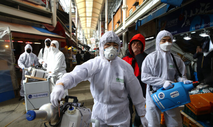 Disinfection professionals wearing protective gear spray anti-septic solution against the coronavirus at a traditional market in Seoul on Feb. 26, 2020. (Chung Sung-Jun/Getty Images)