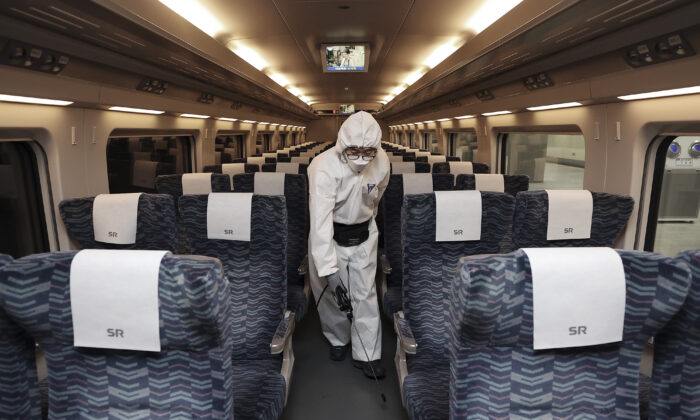 A worker wearing protective gears sprays disinfectant as a precaution on a train against the new coronavirus at Suseo Railway Station in Seoul, South Korea on Feb. 25, 2020. (Lee Ji-eun/Yonhap via AP)