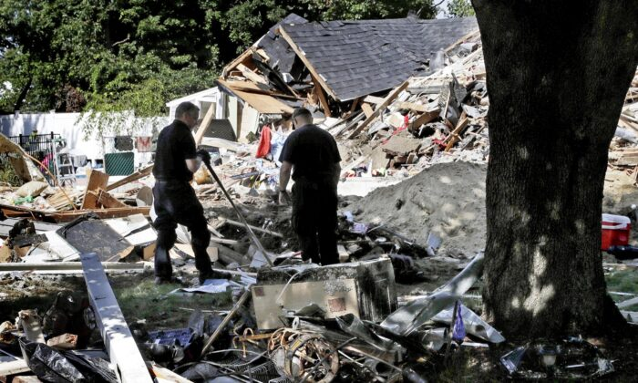 Fire investigators pause while searching the debris at a home which exploded following a gas line failure in Lawrence, Mass., on Sept. 21, 2018. (Charles Krupa/AP Photo/File)