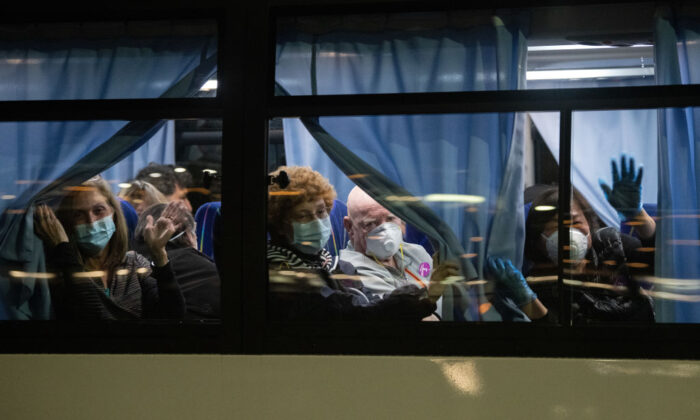 American citizens wave from a bus as they leave the quarantined Diamond Princess cruise ship at Daikoku Pier to be repatriated to the United States on Feb. 17, 2020, in Yokohama, Japan. Some passengers who have tested positive for coronavirus may be transferred to a facility in Costa Mesa, Calif. (Carl Court/Getty Images)