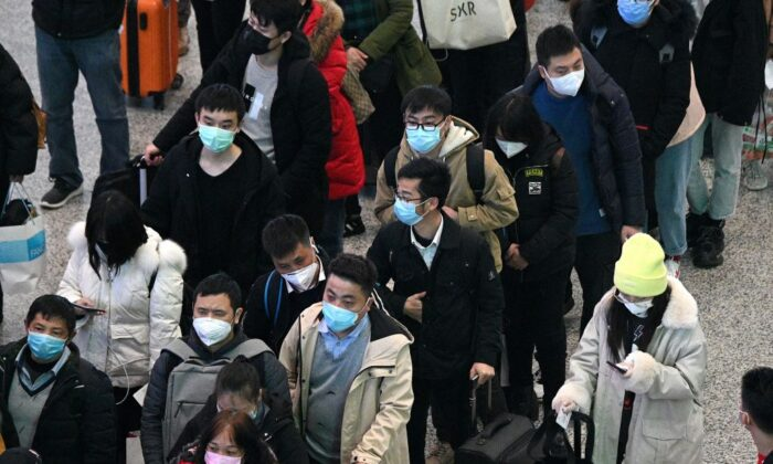 Passengers wearing protective face masks arrive at the Hongqiao railway station in Shanghai on Feb. 26, 2020. (Noel Celis/AFP via Getty Images)