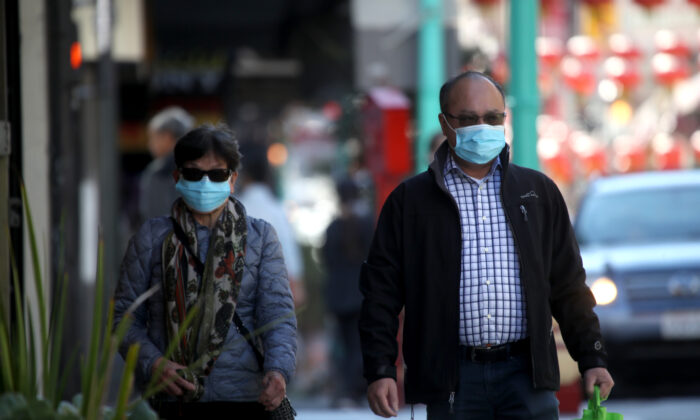 People wear surgical masks as they walk along Chinatown's Grant Avenue in San Francisco, California on Feb. 26, 2020. (Justin Sullivan/Getty Images)