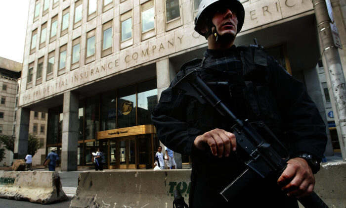 A heavily armed Newark Police officer stands guard outside the Prudential Insurance Company building in Newark, N.J., on Aug. 10, 2004. (Chris Hondros/Getty Images)
