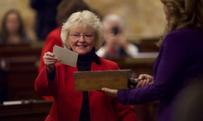 An elector places her signed ballot into a ballot box in the House of Representatives chamber of the Pennsylvania Capitol Building in Harrisburg on Dec. 19, 2016. (Mark Makela/Getty Images)