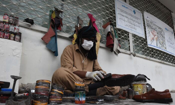 A cobbler wears a protective facemask as a prevention measure against COVID-19 coronavirus as he polishes shoes in a street in Quetta, Pakistan, on Feb. 27, 2020. (Banaras Khan /AFP via Getty Images)