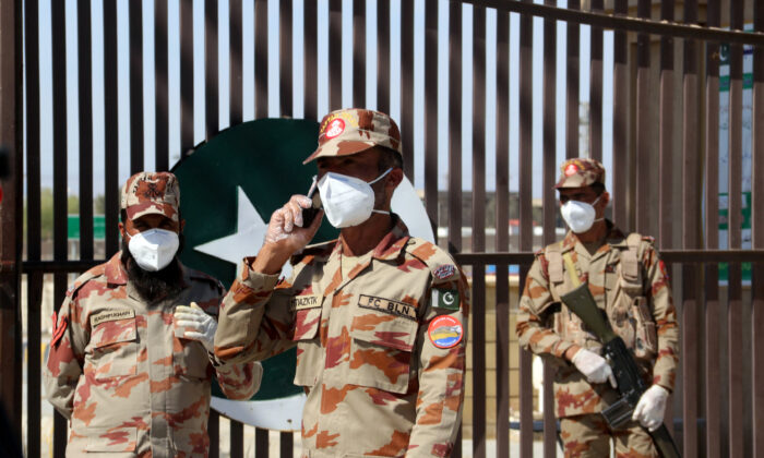 Paramilitary soldiers wear face masks as they stand in front of a closed gate of Pakistan's border post, after Pakistan sealed its border with Iran as a preventive measure following the coronavirus outbreak, at the border post in Taftan, Pakistan, on Feb. 25, 2020. (Naseer Ahmed/Reuters)