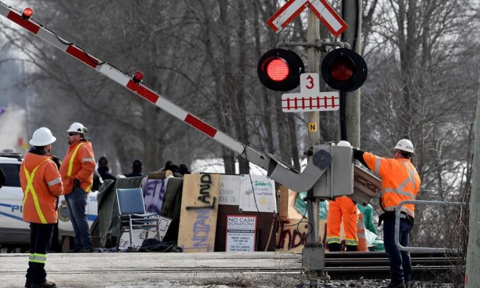 CN Railway workers check the railroad crossing gate as they prepare to resume service after Ontario Provincial Police made arrests at a rail blockade in Tyendinaga Mohawk Territory, near Belleville, Ont., on Feb. 24, 2020, during a protest in solidarity with Wet'suwet'en Nation hereditary chiefs attempting to halt construction of a natural gas pipeline on their traditional territories. (Adrian Wyld/The Canadian Press)
