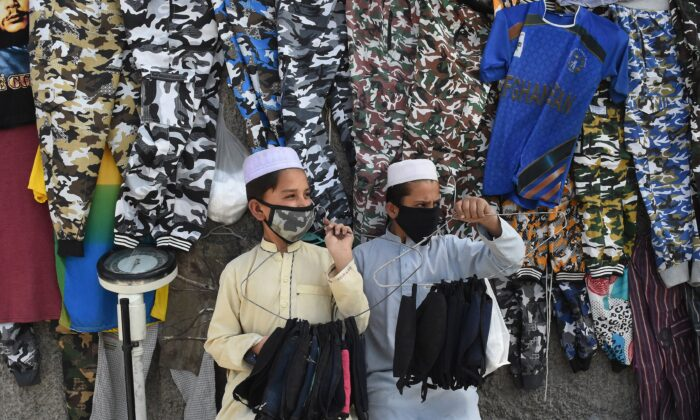Facemask vendors wear protective facemasks as a prevention measure against the COVID-19 coronavirus alongside a street in Quetta, Pakistan on Feb. 27, 2020. The country reported its first confirmed cases. (Banaras Khan/AFP via Getty Images)