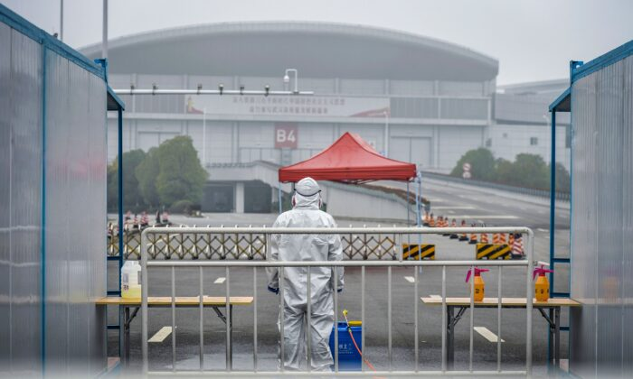 A medical staff wearing protective gear looking on outside a makeshift hospital in Wuhan in China's central Hubei province. - Chinese authorities on February 24 slightly relaxed their month-long quarantine measures in Wuhan, allowing some people to leave the epicentre of the country's virus epidemic under certain conditions, on Feb. 22, 2020. (STR/AFP via Getty Images)