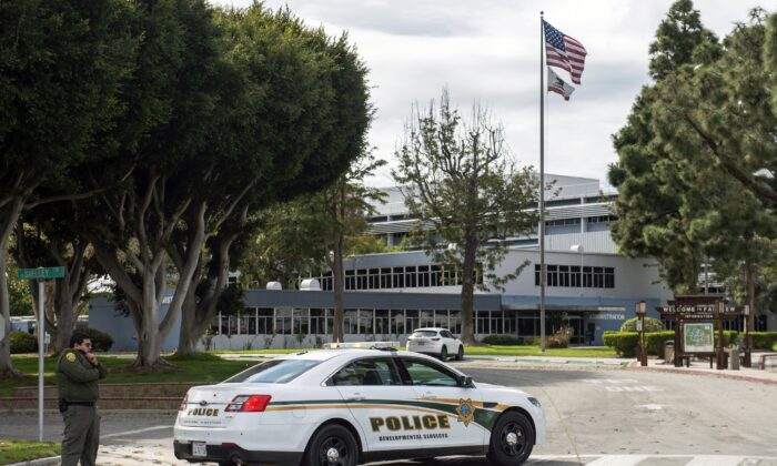 In this Feb. 22, 2020, file photo, a police officer stands guard by the Fairview Development Center in Costa Mesa, Calif., after if was announced that the center may be used to house coronavirus patients. (Mindy Schauer/The Orange County Register via AP)