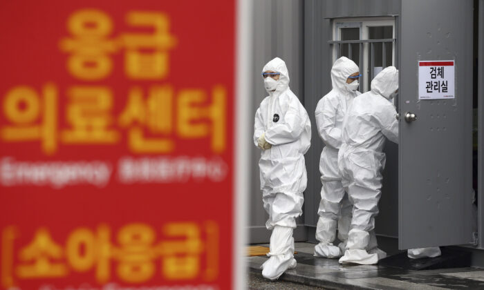 Officials wearing protective attire work to diagnose people with suspected symptoms of the new coronavirus at a hospital in Daegu, South Korea, on Feb. 26, 2020. (Kim Hyun-tae/Yonhap via AP)