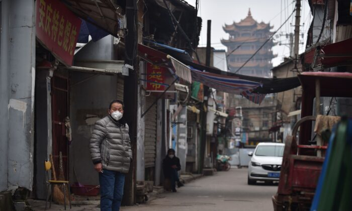 A man wears a face mask as a preventive measure against the COVID-19 coronavirus in an alley in Wuhan, in China's central Hubei Province, on Feb. 26, 2020. (STR/AFP via Getty Images)