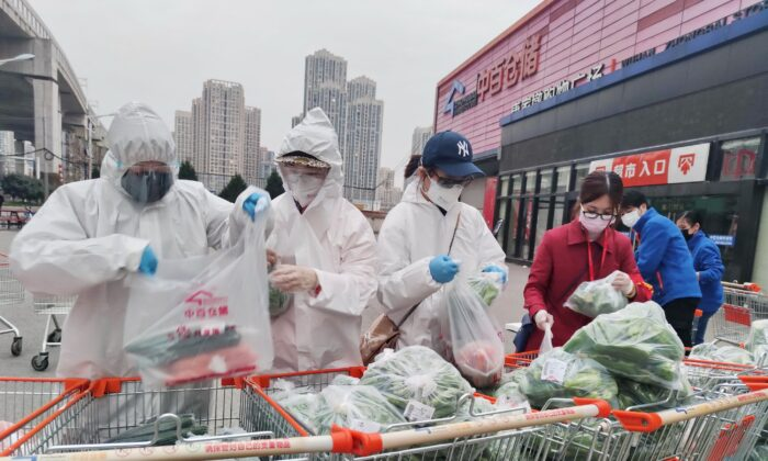 Community workers and volunteers wearing face masks sort and pack groceries from a supermarket purchased through group orders after supermarkets stopped selling to individuals, in Wuhan, the epicenter of the novel coronavirus outbreak, in Hubei Province, China on Feb. 24, 2020. (China Daily via Reuters)