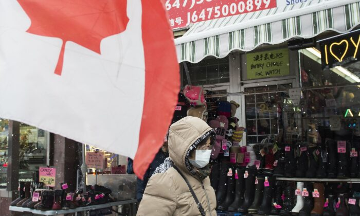 A pedestrian wears a protective mask as she walks in downtown in Toronto on Feb. 26, 2020. Canada's top public-health official Dr. Theresa Tam says Canada has begun to look at tracking local spread of the novel coronavirus. (The Canadian Press/Nathan Denette)