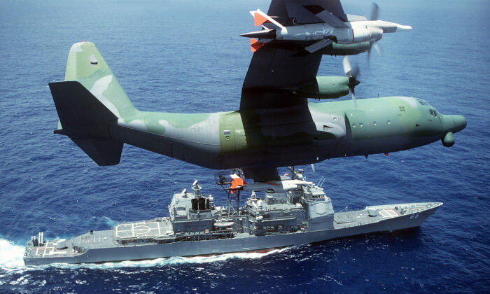 A DC-130H Hercules drone control aircraft banks to the left while passing over the guided missile cruiser USS CHOSIN (CG-65). (Photo by USAF)