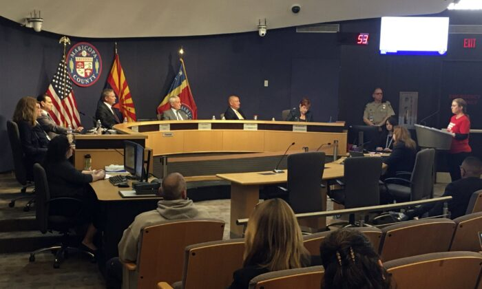 The Maricopa County Board of Supervisors listens to comments from Marie Thearle, right, a gun control supporter, during a meeting in Phoenix on Feb. 26, 2020. (Terry Tang/AP Photo)