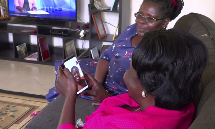 Margaret Ntale, whose three student daughters are stranded in Wuhan, and Cecilia Oyet, in foreground holding cellphone, whose daughter is a medical student at Wuhan University of Science and Technology, speak by video-call to their children and other Ugandan students who are stranded in Wuhan, from Ntale's house in Kampala, Uganda on Feb. 27, 2020. Parents' fears are growing for the thousands of African students who are thought to be stranded in Wuhan amid the virus outbreak, with concerns that students are running out of food and money weeks after other countries evacuated citizens. (AP Photo)