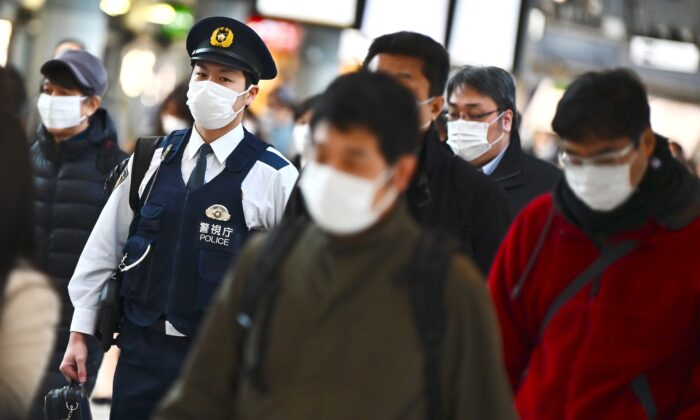 Mask-clad commuters make their way to work during morning rush hour at the Shinagawa train station in Tokyo on Feb. 28, 2020. (Charly Triballeau/AFP via Getty Images)