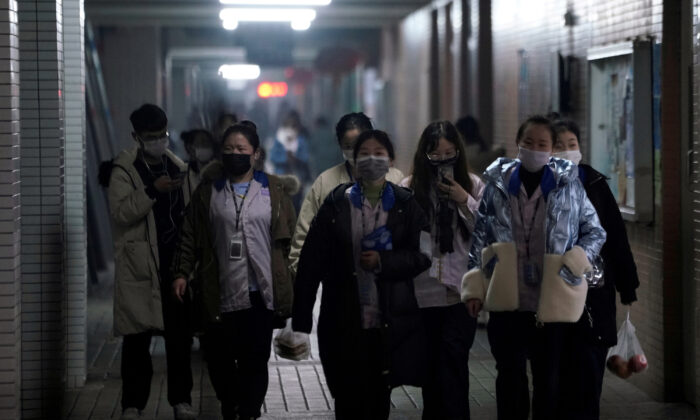 Workers wearing masks walk outside their dormitory, in an electronics manufacturing factory in Shanghai, China, as the country is hit by an outbreak of a new coronavirus, on Feb. 12, 2020. (Aly Song/Reuters)