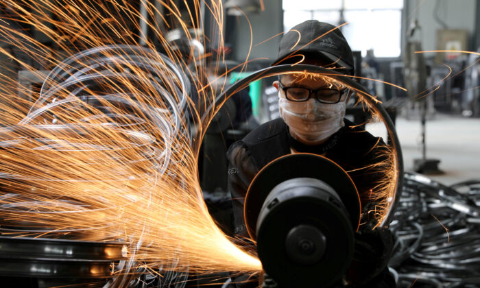 A worker welds a bicycle steel rim at a factory manufacturing sports equipment in Hangzhou, Zhejiang Province, China, on Sept. 2, 2019. (China Daily via Reuters)