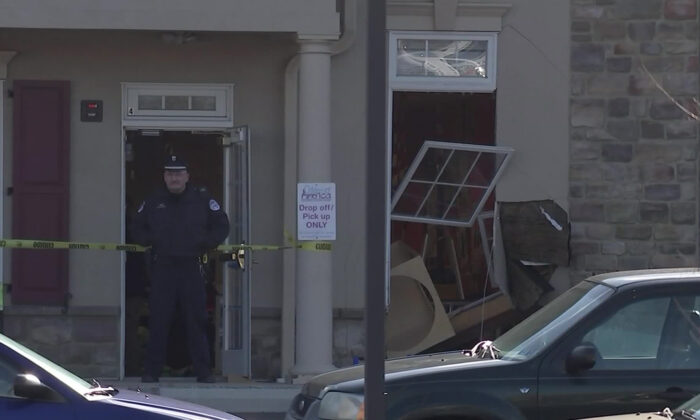 A police officer stands outside a day care center after a car crashed through the window of the center, in Pennsylvania on Feb. 27. 2019. (Courtesy of KYW)