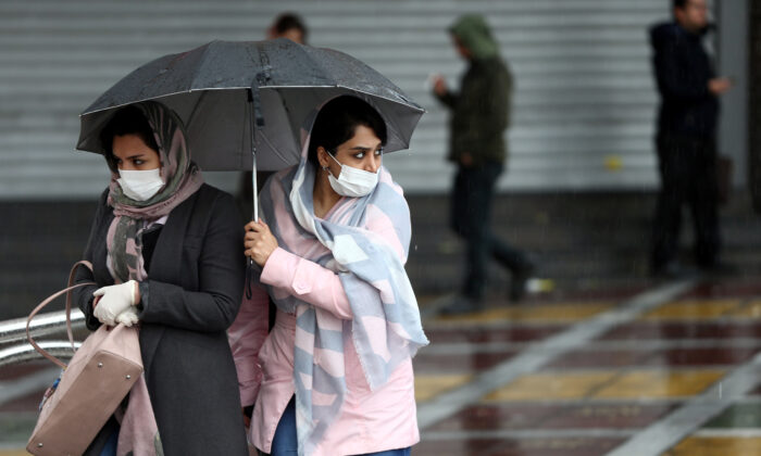 Iranian women wear protective masks to prevent spreading the coronavirus, as they walk in the street in Tehran, Iran on Feb. 25, 2020. (Nazanin Tabatabaee/West Asia News Agency via Reuters)