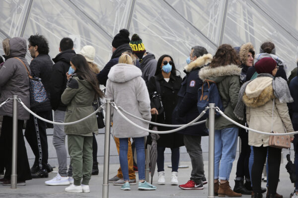 Tourists, some wearing a mask, queue to enter the Louvre museum