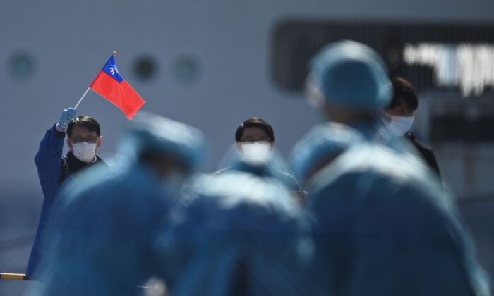 A man (L) holds a Taiwan flag as passengers disembark from the Diamond Princess cruise ship, in quarantine due to fears of new COVID-19 coronavirus, at the Daikoku pier cruise terminal in Yokohama on Feb. 21, 2020. (Philip Fong/AFP via Getty Images)