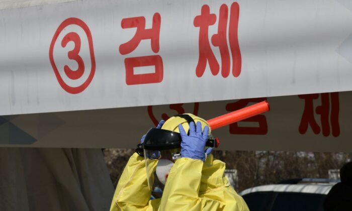 "A medical member wearing protective gear guides drivers with suspected symptoms of the COVID-19 coronavirus, at a ""drive-through"" virus test facility in Goyang, north of Seoul, on Feb. 29, 2020. (Jung Yeonje-JE/AFP via Getty Images)"