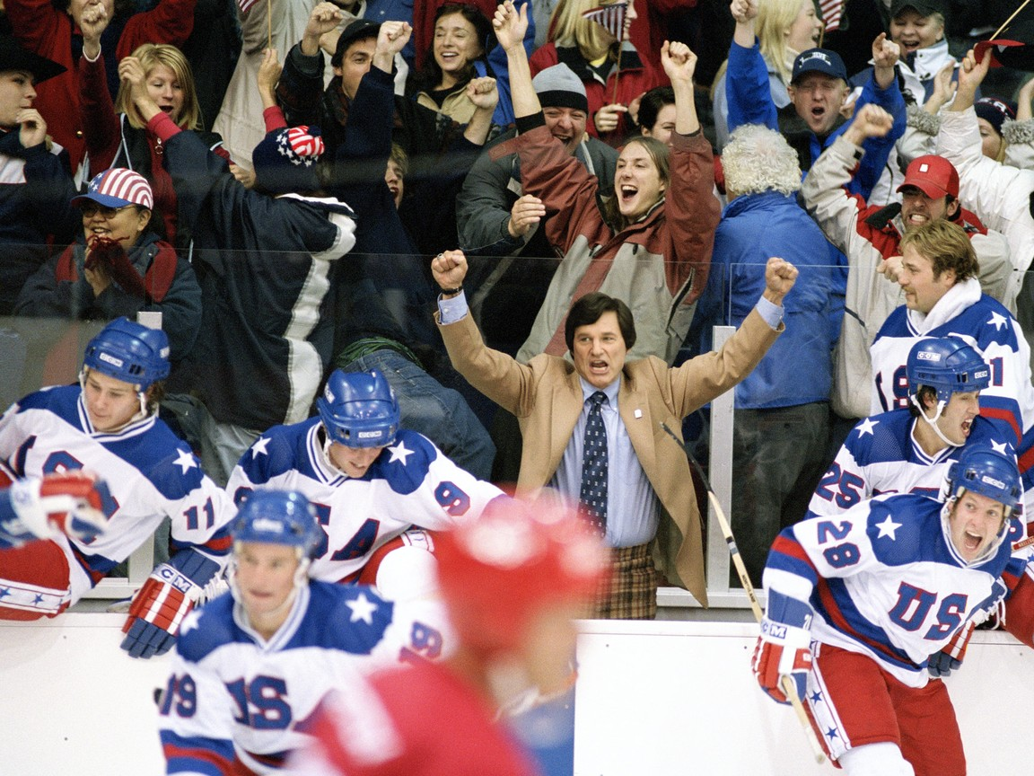 coach with arms raised, hockey team celebrating
