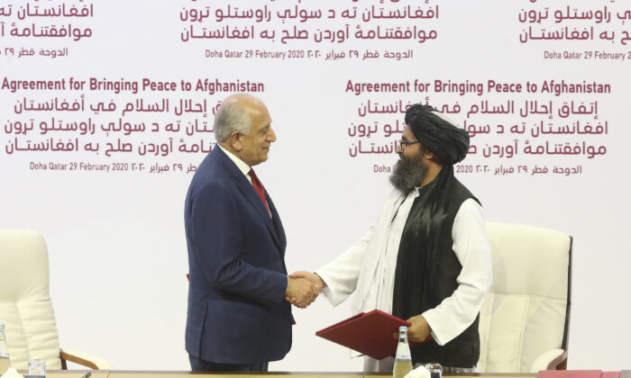U.S. peace envoy Zalmay Khalilzad (L), and Mullah Abdul Ghani Baradar, the Taliban group's top political leader shack hands after signing a peace agreement between Taliban and U.S. officials in Doha, Qatar, on Feb. 29, 2020. (AP Photo/Hussein Sayed)