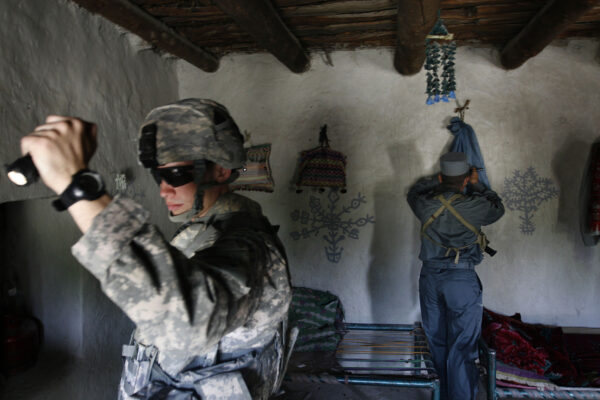 U.S. First Lt. Shane Oravsky, left, of the 101st Airborne Division searches a house