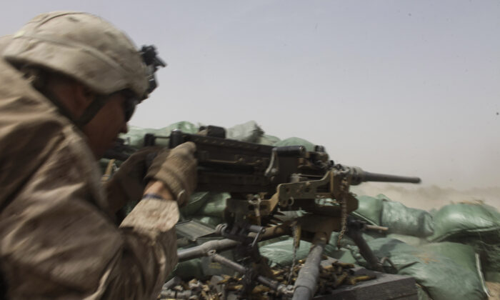 A U.S. Marine fires a heavy machine gun to counter Taliban fire from a nearby treeline, during a firefight in Helmand province, southern Afghanistan, on Aug. 25, 2011. (Brennan Linsley/AP)