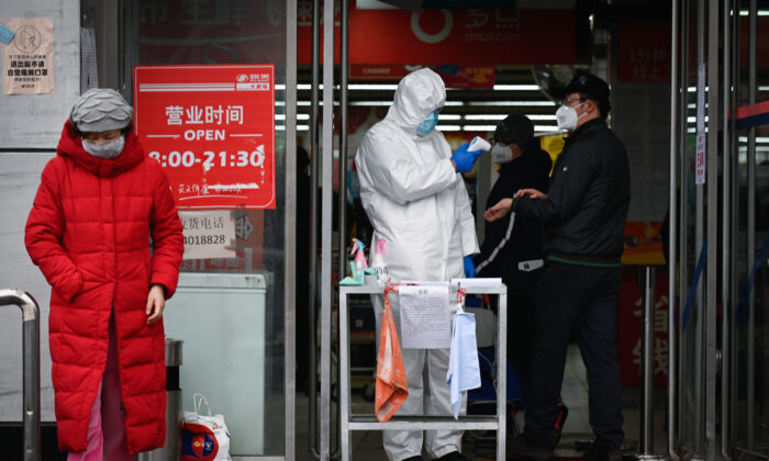 A staff member of a supermarket wearing a protective suit uses a thermometer to check the temperature of customers at the entrance of a supermarket in Beijing on Feb. 29, 2020. (STR/AFP via Getty Images)