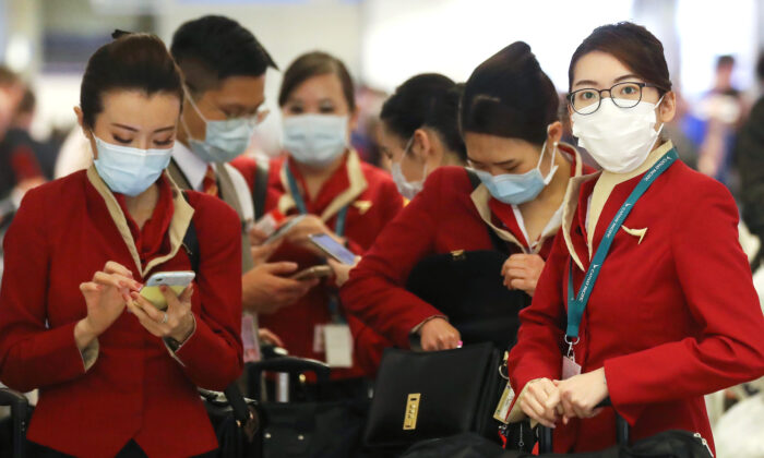 A flight crew from Cathay Pacific Airways wearing protective masks stand in the international terminal after arriving on a flight from Hong Kong at Los Angeles International Airport in Los Angeles, California, on Feb. 28, 2020. (Mario Tama/Getty Images)