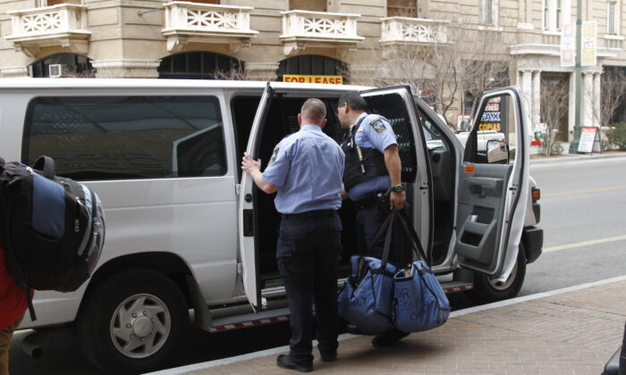 Immigration guards finish loading a van of immigrants leaving court under guard in El Paso, Texas, on Feb. 28, 2020. (Cedar Attanasio/AP Photo)