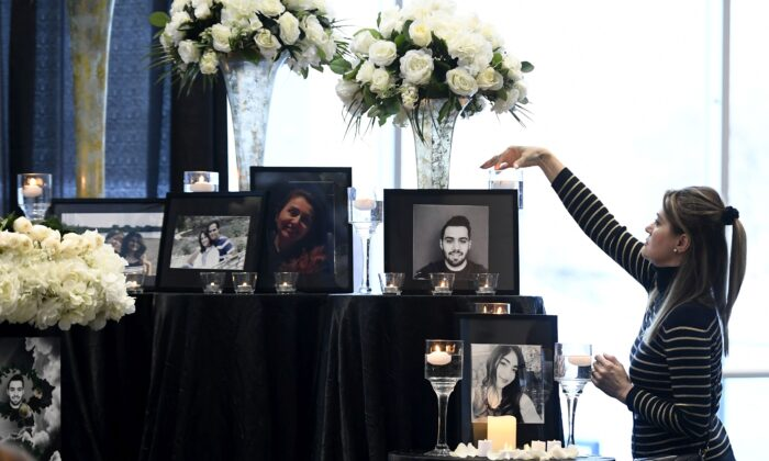 A woman lights a candle in front of a memorial before a ceremony for Ottawa area victims of Ukraine International Airlines Flight PS752, at Ottawa City Hall on Jan. 19, 2020. (The Canadian Press/Justin Tang)