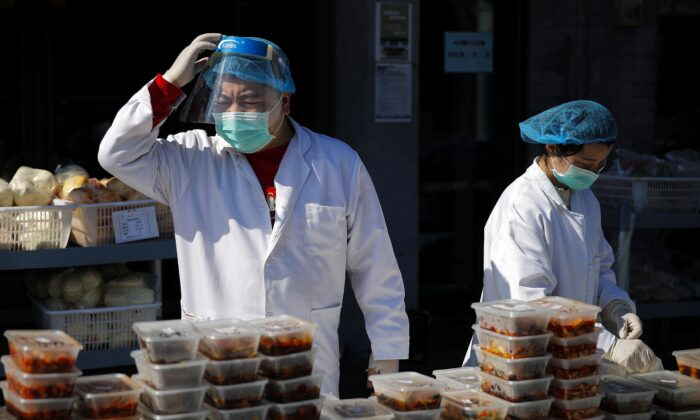 Workers wearing protective gear prepare food orders outside a restaurant only offering take-out to prevent people gathering due to the coronavirus outbreak, in Beijing on March 1, 2020. (AP Photo/Andy Wong)