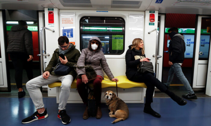 A woman wearing a protective mask and her dog sit on the subway in Milan, Italy, on March 1, 2020. (Yara Nardi/Reuters)