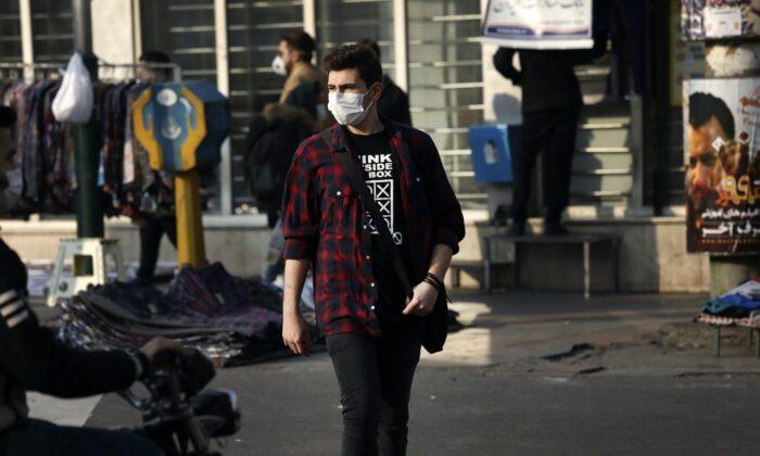 A pedestrian wearing a face mask crosses a street in western Tehran, Iran, on Feb. 29, 2020. (Vahid Salemi/AP Photo)