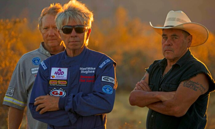 """The late daredevil """"Mad"""" Mike Hughes (C) stands with friends and collaborators, Waldo Stakes (R) and Patrick Marchese (L), ahead of one of many launches Hughes made in homemade rockets, this one in Amboy, Calif., on March 24, 2018. (Toby Brusseau)"""
