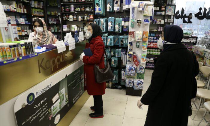 Customers wait as a pharmacist prepares medicines at a pharmacy in western Tehran, Iran, on Feb. 29, 2020. (Vahid Salemi/AP Photo)