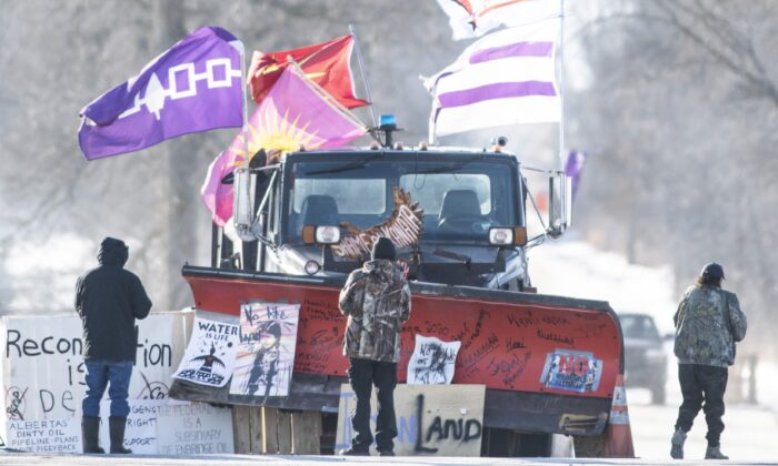 Protesters look at signatures written on the blade of a snowplow parked adjacent to the closed rail line near Belleville, Ont., in Tyendinaga Mohawk Territory, on Feb. 20, 2020. (The Canadian Press/Justin Tang)