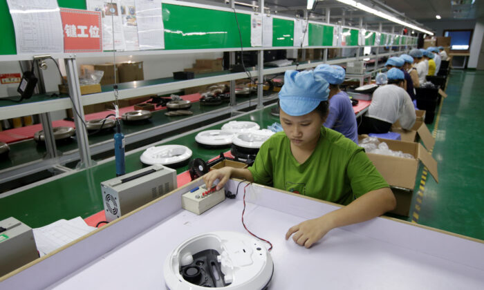 An employee works on the production line of a robot vacuum cleaner factory of Matsutek in Shenzhen, China, on Aug. 9, 2019. (Jason Lee/Reuters)